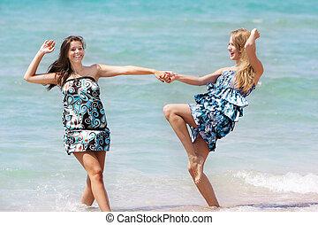two young girl having fun on beach
