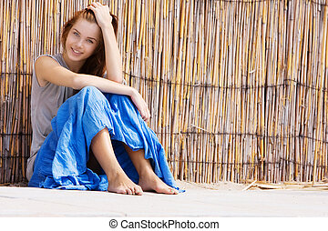 young happy girl sitting near bamboo wall
