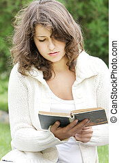 young girl reading book outdoors