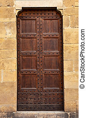 Wooden closed brown door with iron nails.