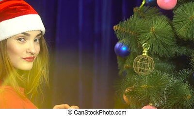 beautiful young girl in santa hat decorates a christmas tree...