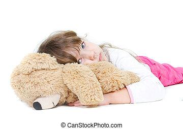 sad young girl embracing teddybear over white