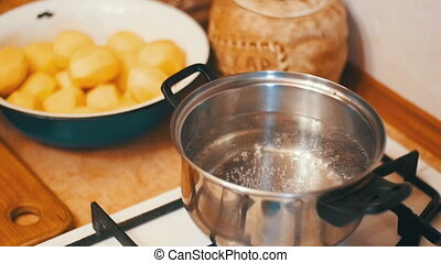 Pan of boiling water on the stove in a home kitchen. Slow...