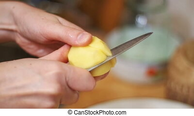 Peeling Potatoes in the Home Kitchen. Slow Motion - Peeling...