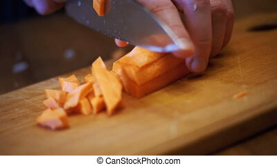 Cutting Carrots into Slices on Chopping Board in Home...