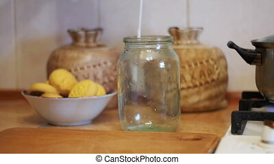 Milk is Poured into a Transparent Jar on a Background of...