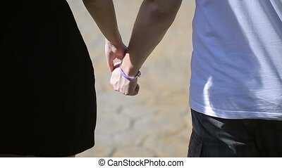 Lovely couple holding hands and walking at sunny day