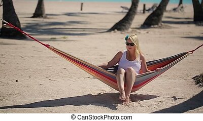 Young blonde woman in hammock on the beach