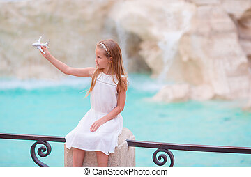 Adorable little girl with toy airplane background Trevi...