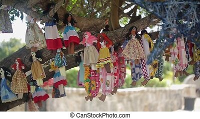 Voodoo dolls on a tree at sunny day