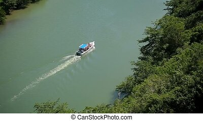 Passenger ship on a river in tropical forest top view