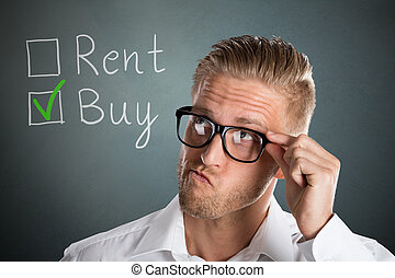 Business Man Choosing Rent Or Buy Option - Young Handsome...