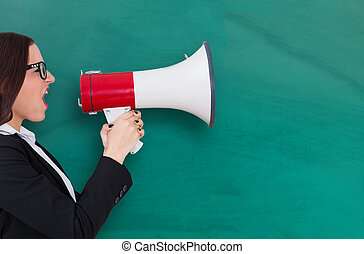 Businesswoman Using Megaphone Against Blackboard - Young...