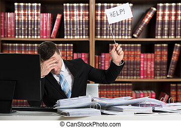 Overworked Accountant Holding Help Sign At Desk - Overworked...