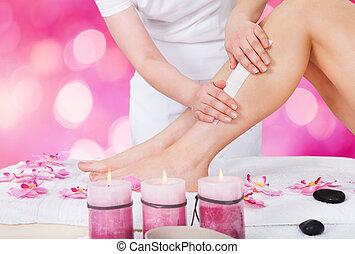 Beautician Waxing Woman Leg With Wax Strip - Close-up Of A...