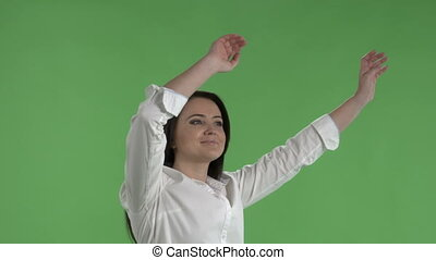 Happy woman waving hands in air to rhythm of music against a...