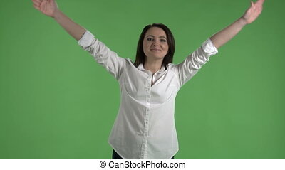 Cheerful woman waving her arms against a green screen -...