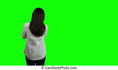 Rear view of woman in white shirt looking at something against green screen