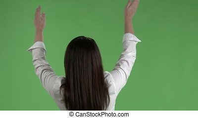 Rear view of woman waving hands in air to rhythm of music against a green screen