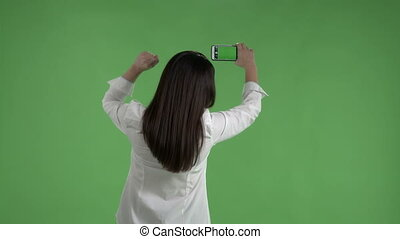 woman with raised fist taking pictures with camera phone...