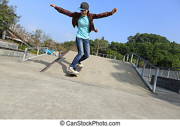 young skateboarder riding skateboard at skatepark