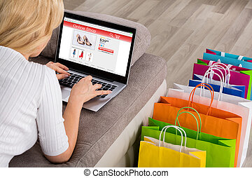 Close-up Of Woman Shopping Online Using Laptop