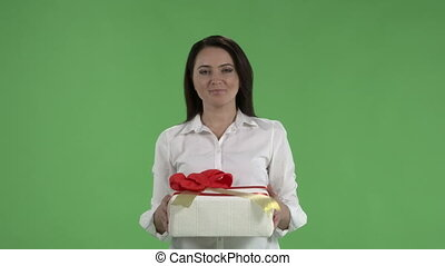 Slow motion woman giving gift box looking at the camera against green screen