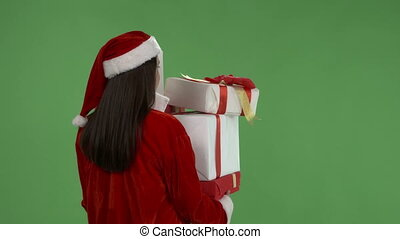 Woman wearing Santa Clause costume with Christmas presents against green screen