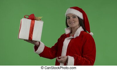 Woman wearing Santa Clause clothes showing white gift box against green screen