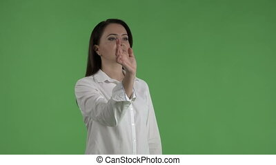 Business woman using an invisible touchscreen against green screen