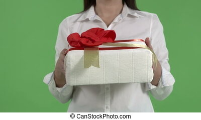 Close-up of female hands giving gift box against green...