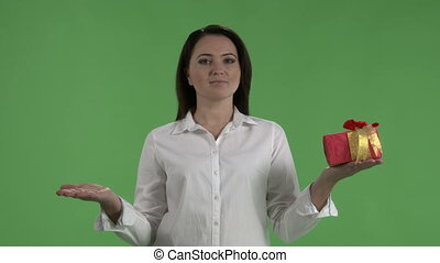 Woman making choice between two gift boxes against green...