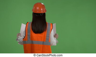 Female construction manager against green screen. Rear view...