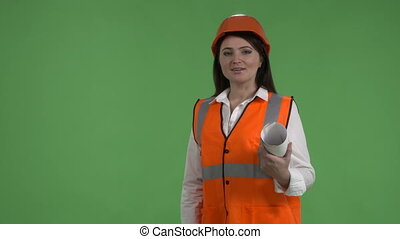 Female construction manager with blueprint on building site against green screen