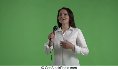 Business woman with microphone speaks to an audience against...