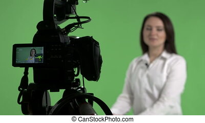 Recording interview in virtual green chroma key studio woman in front of camera