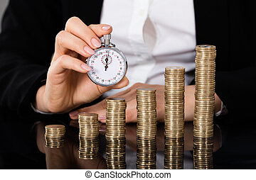 Businesswoman Holding Stopwatch In Front Of Stacked Coin