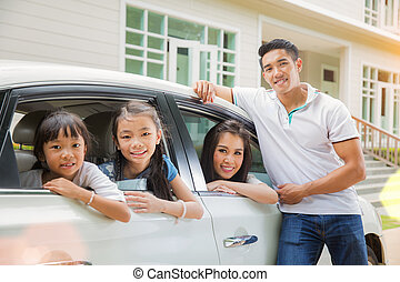 Beautiful family portrait smiling outside their new house,...
