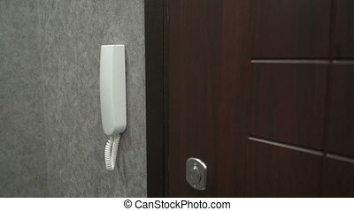 Person holding handset of intercom system installed on a wall in the apartment