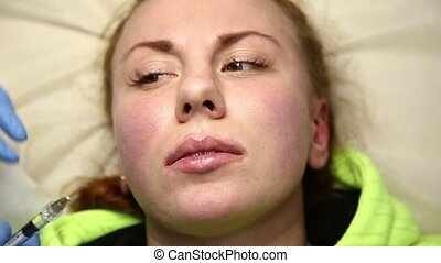 Young woman on lip Augmentation in a clinic. Anesthetic...