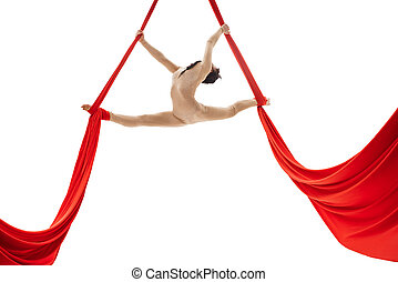 Young girl doing splits on aerial silks in studio - Young...