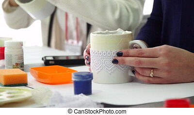 Decor ceramic mugs. Girl makes a gift by hand. Decoration. Slow motion.