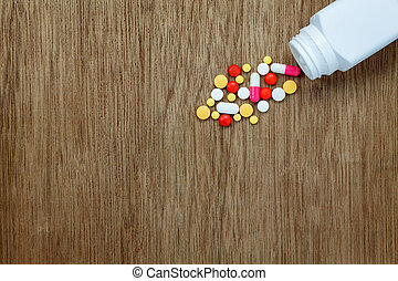 Top view medical concept the colorful medicine and pills spilling of bottle on wooden background.