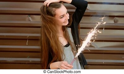 Young teenage girl with sparkler in her hands and make...