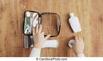 hands packing bag with cosmetics - people, toiletry and...