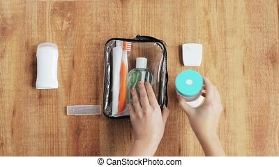 hands packing cosmetic bag for travel - people, toiletry and...