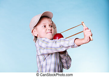 Young boy use sling shot shoot apple. - Nature and free time...