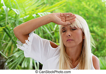 Mature woman with headache in summer heat on her terrace