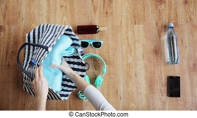 hands packing beach accessories to bag - summer holidays and...