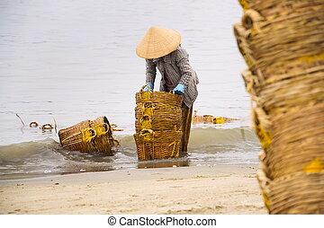 Woman washing baskets on fish sauce production, Mui Ne,...
